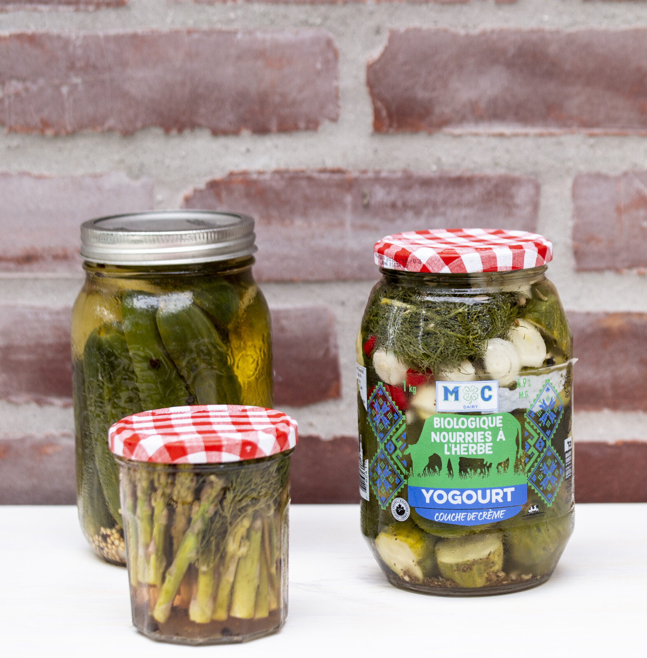 Crunchy dill pickles in three glass bottles