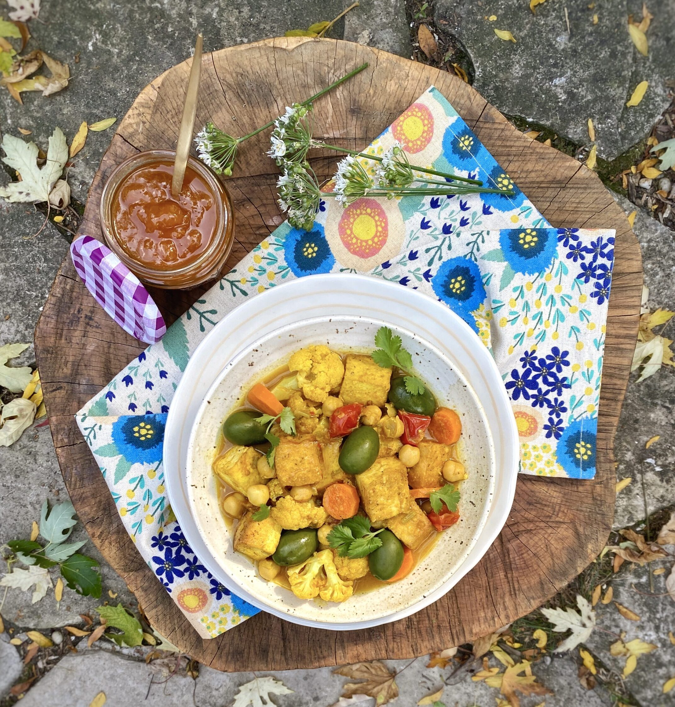 Vegan Spiced Moroccan Tofu tangine made out of hearty vegetables. Photo is outdoors
